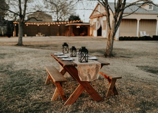 rectangular brown wooden picnic table on the field
