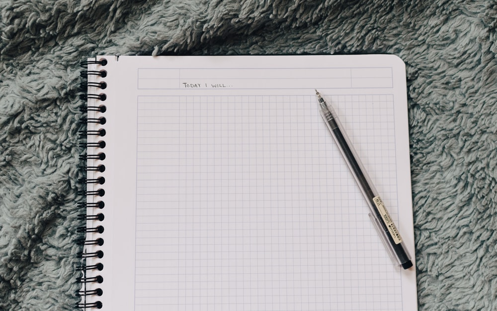 click pen on white notebook