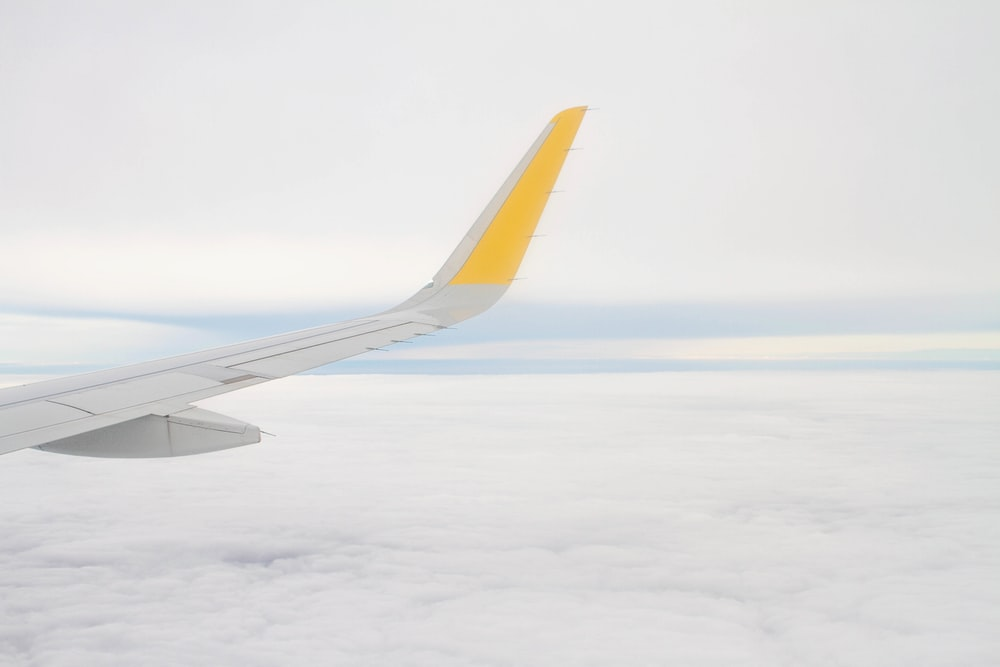 right airplane wing over white clouds during daytime