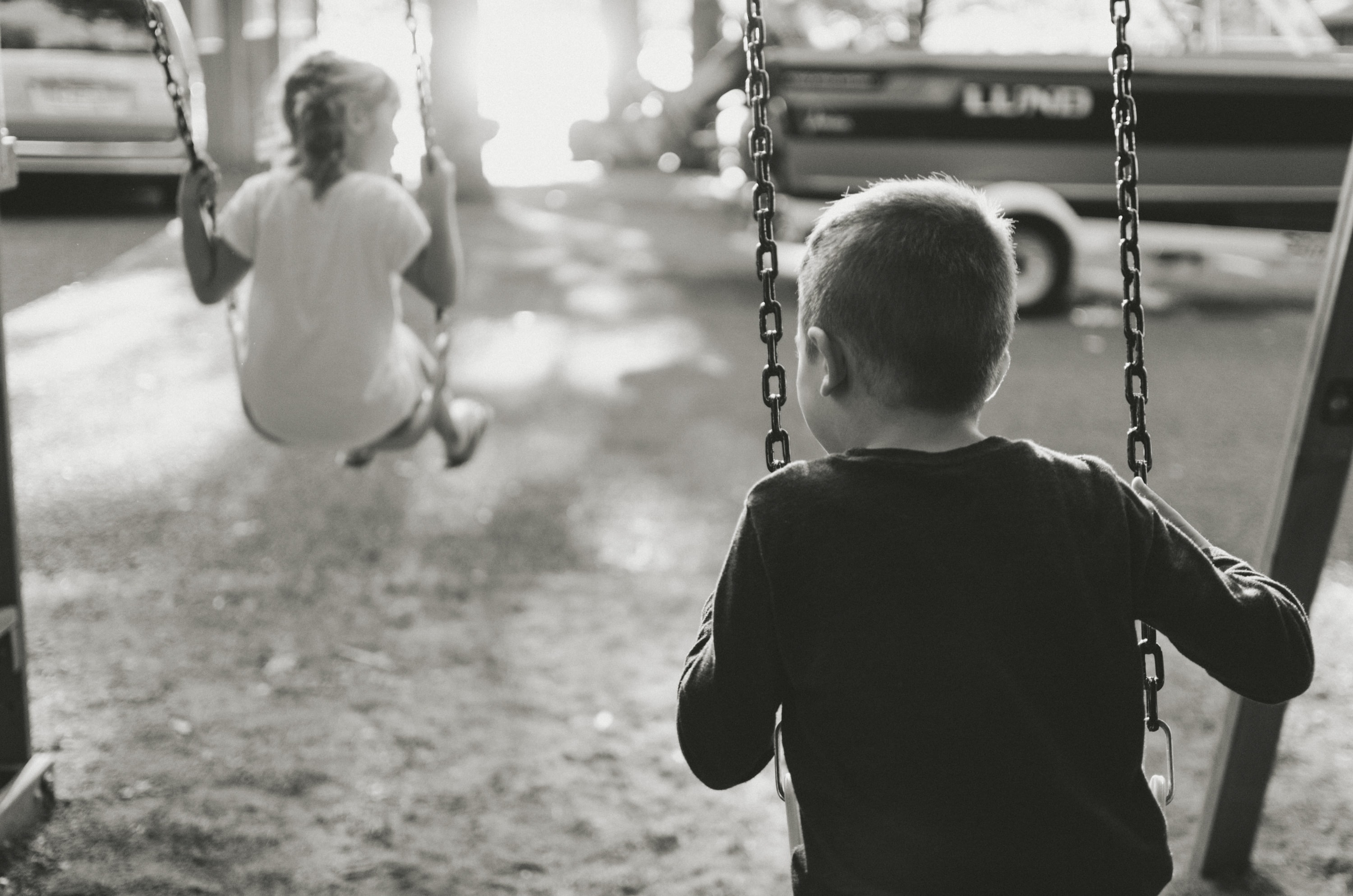 grayscale photography of boy and girl on swing