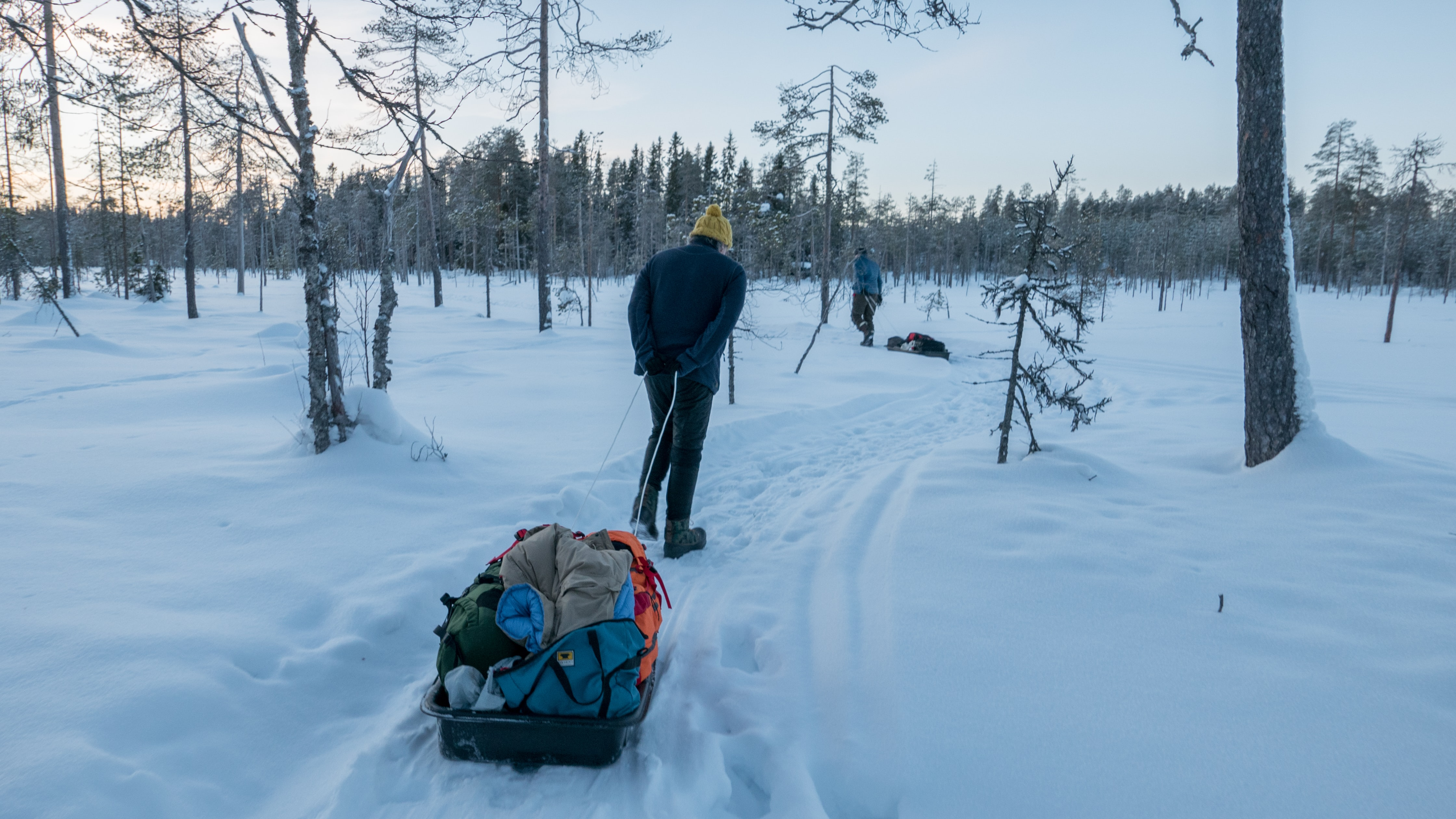 man in blue coat walking on snow pulling grey wagon with luggages near trees during daytime