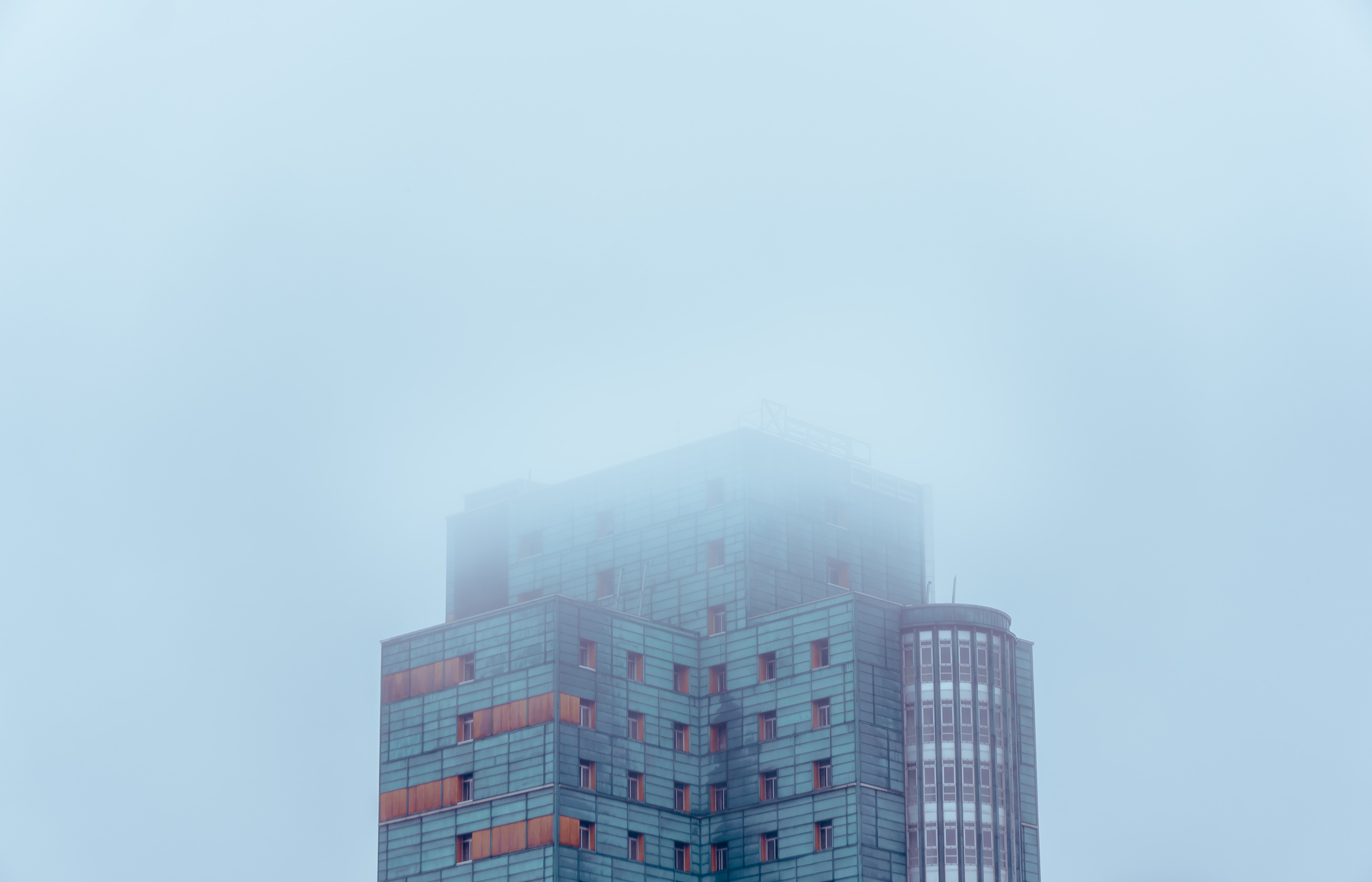 photo of white and blue building covered with clouds