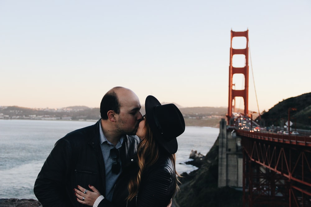 man and woman kissing beside Golden Gate Bridge during daytime