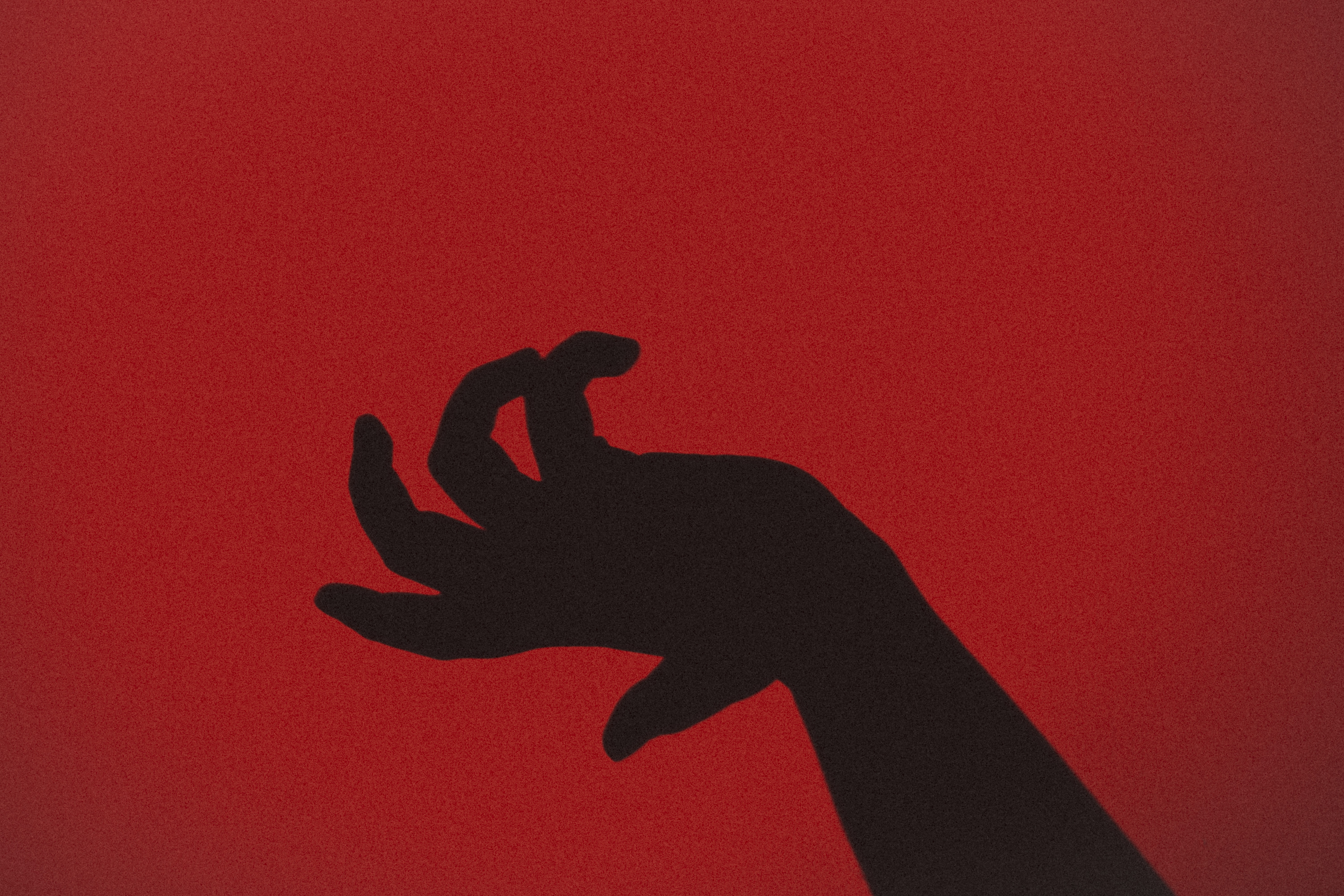 silhouette of hand with red background