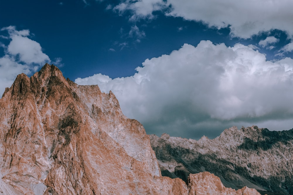 brown rock formations under white clouds at daytime