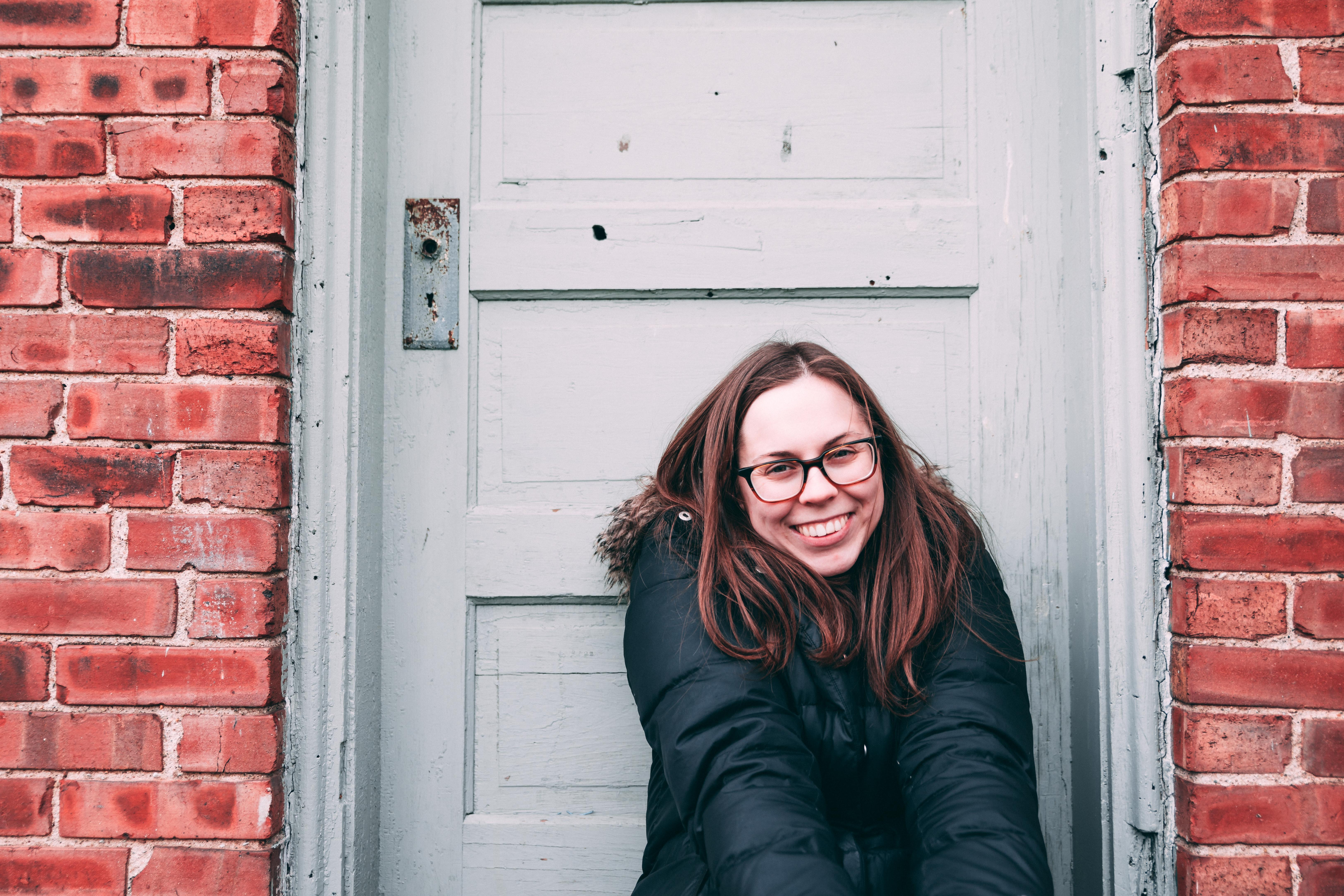 smiling woman sits beside white wooden door during daytime