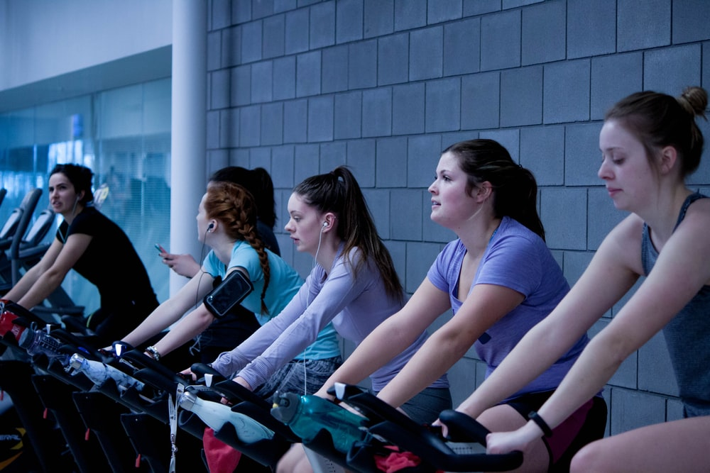 women taking exercise on black stationary bikes in front of gray concrete wall to improve their fitness