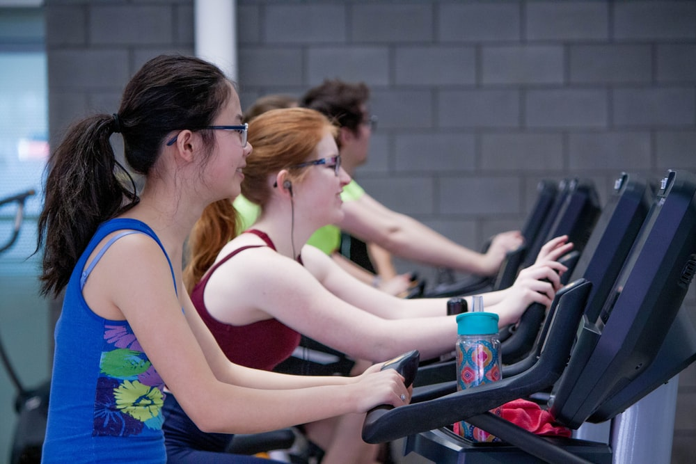 two woman walking on treadmills