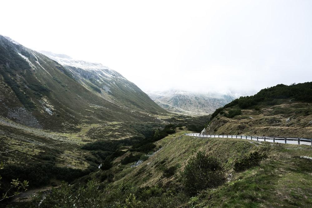 road near mountain under gray sky