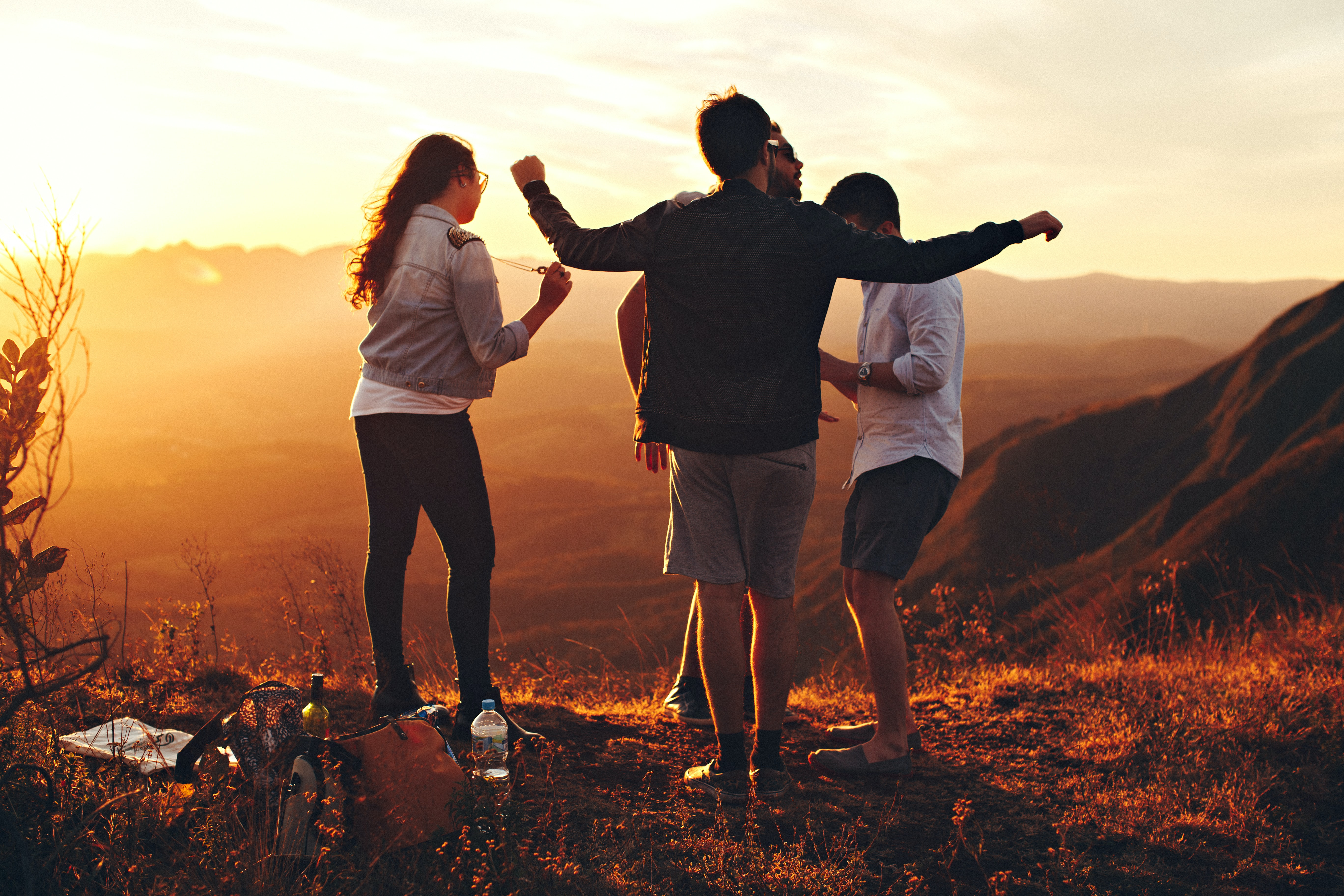 four people standing on edge of mountain