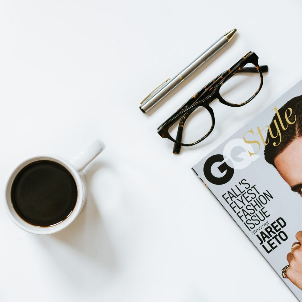 clear eyeglasses with black frame near white ceramic coffee cup