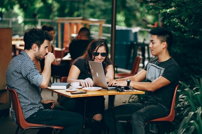 photo of three person sitting and talking