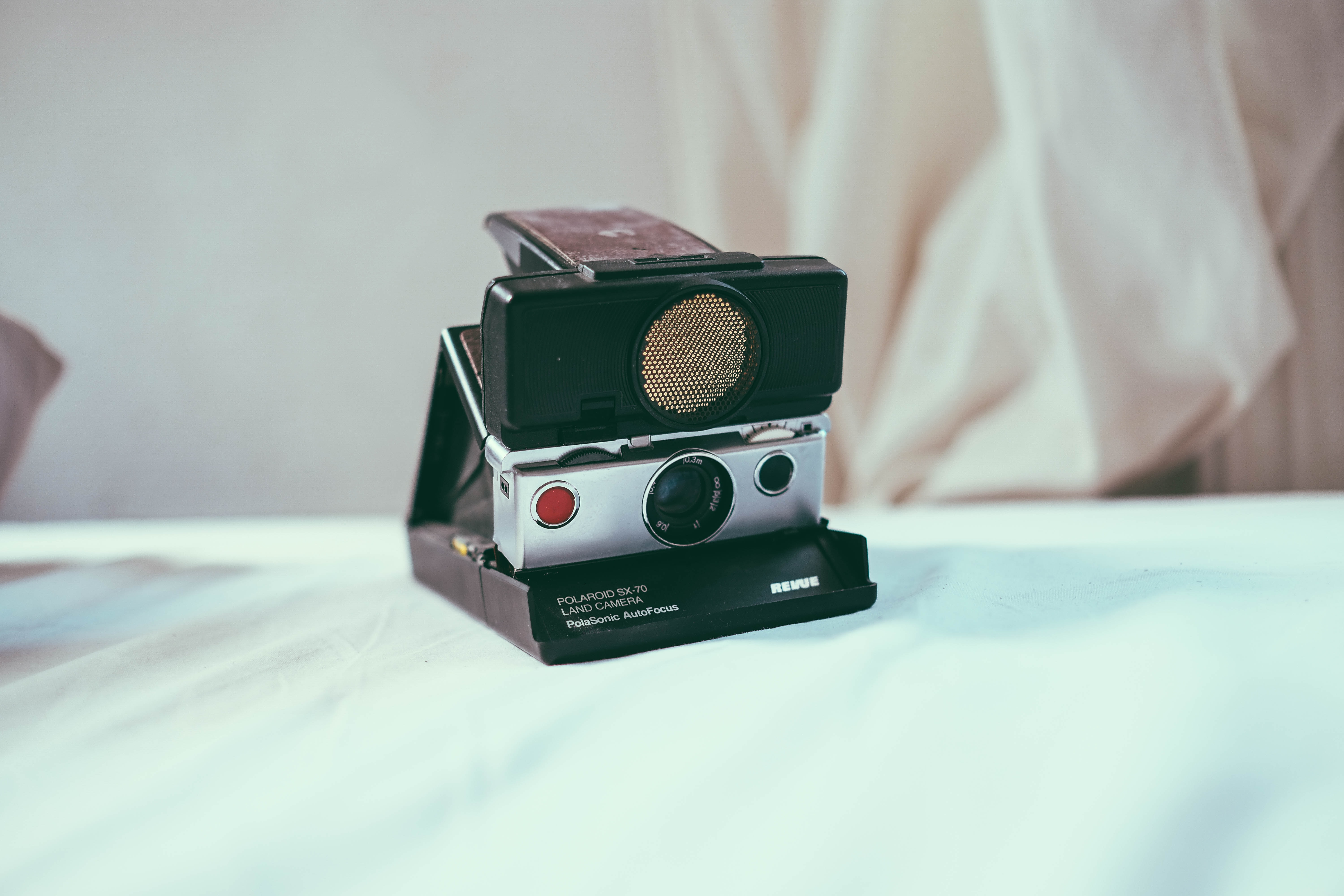black and gray instant camera on white table