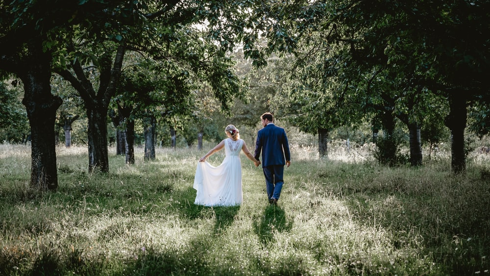 bride and groom walking on grass field between treeline photo