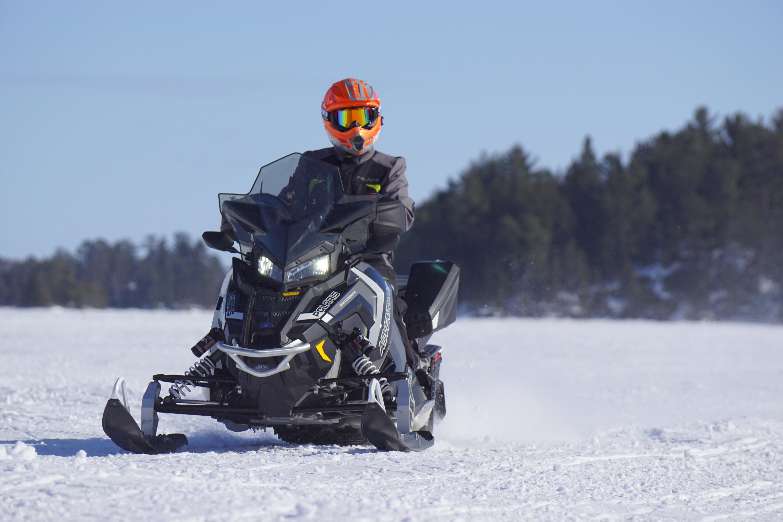 man riding on black snowmobile
