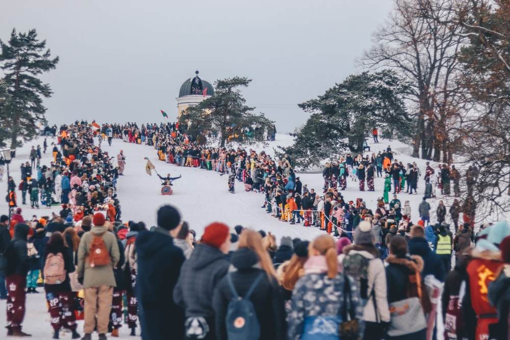 people stands on snow and watches sled race during daytime