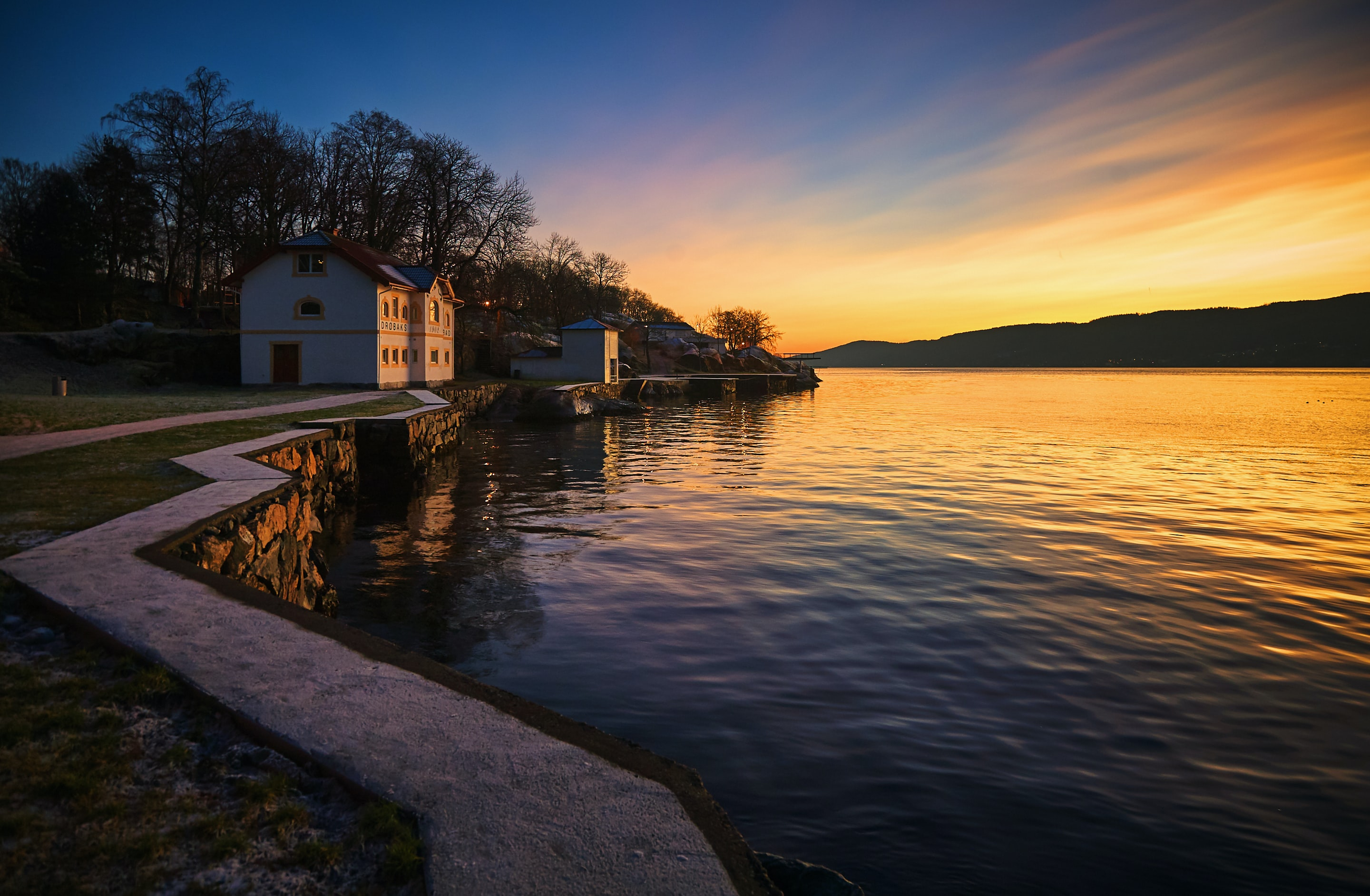 landscape photography of house with pathway near bay