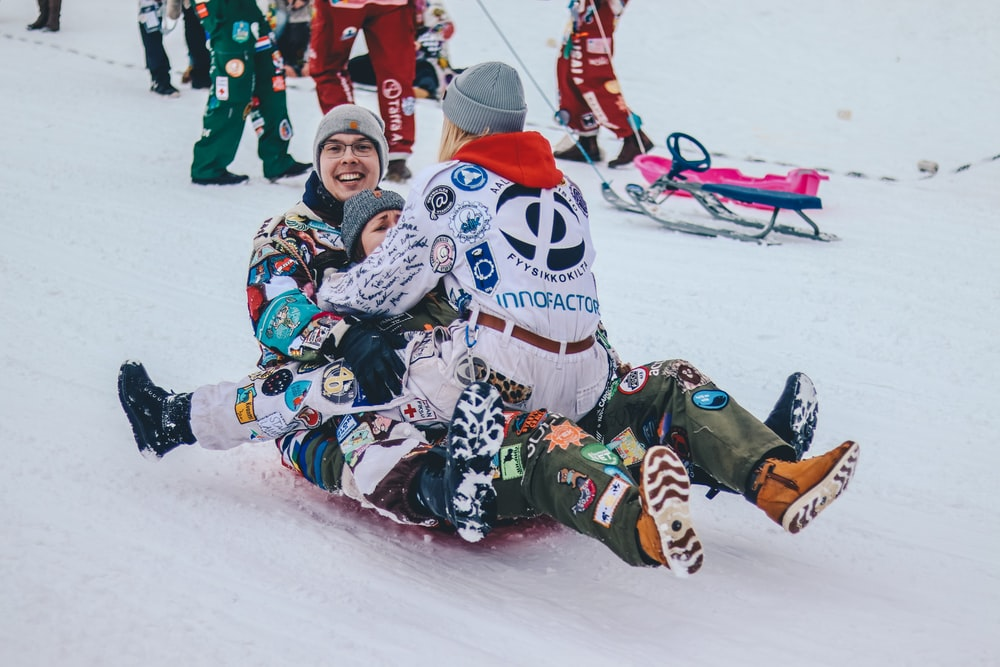three persons riding on sled