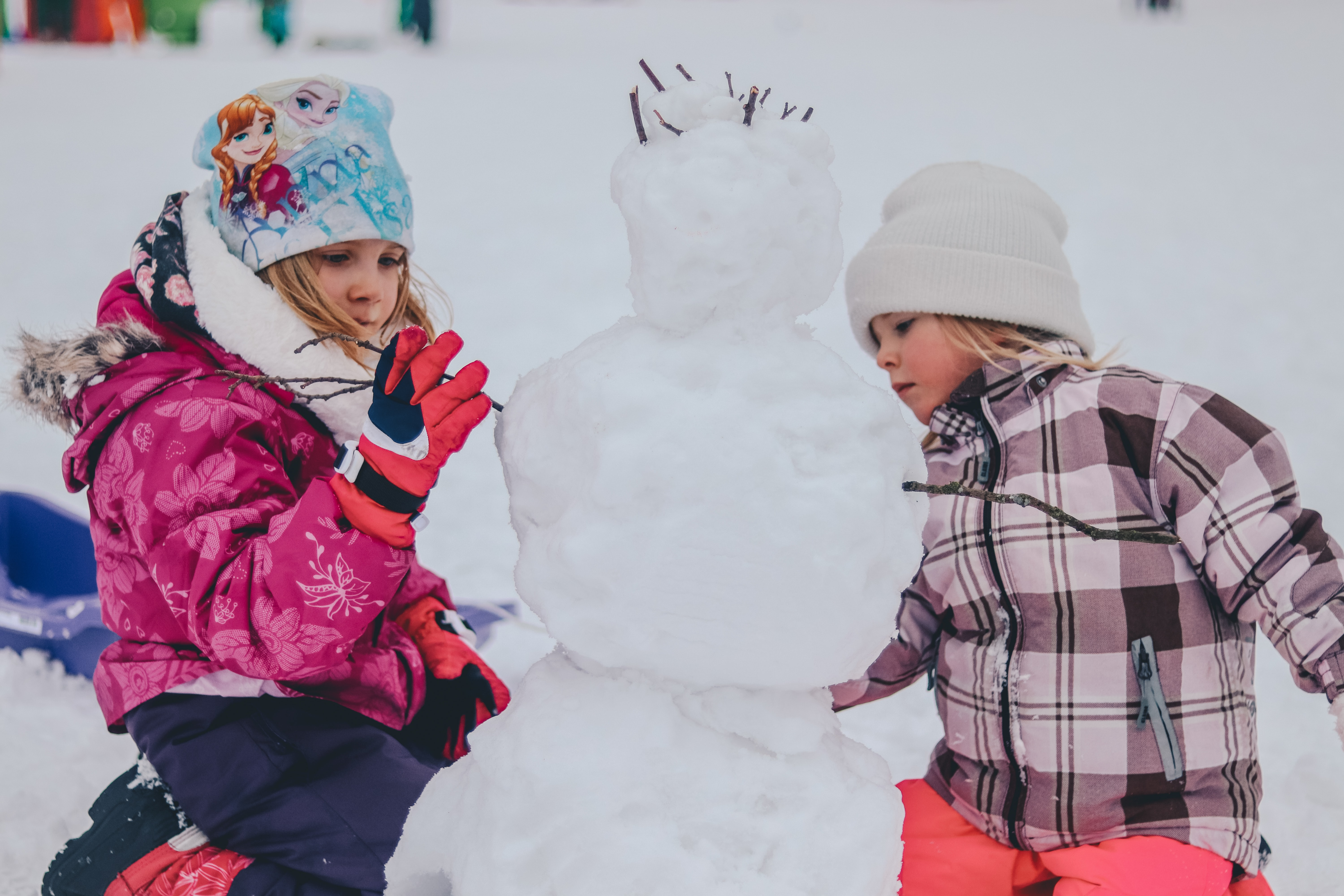 two girl molding a snowman during daytime