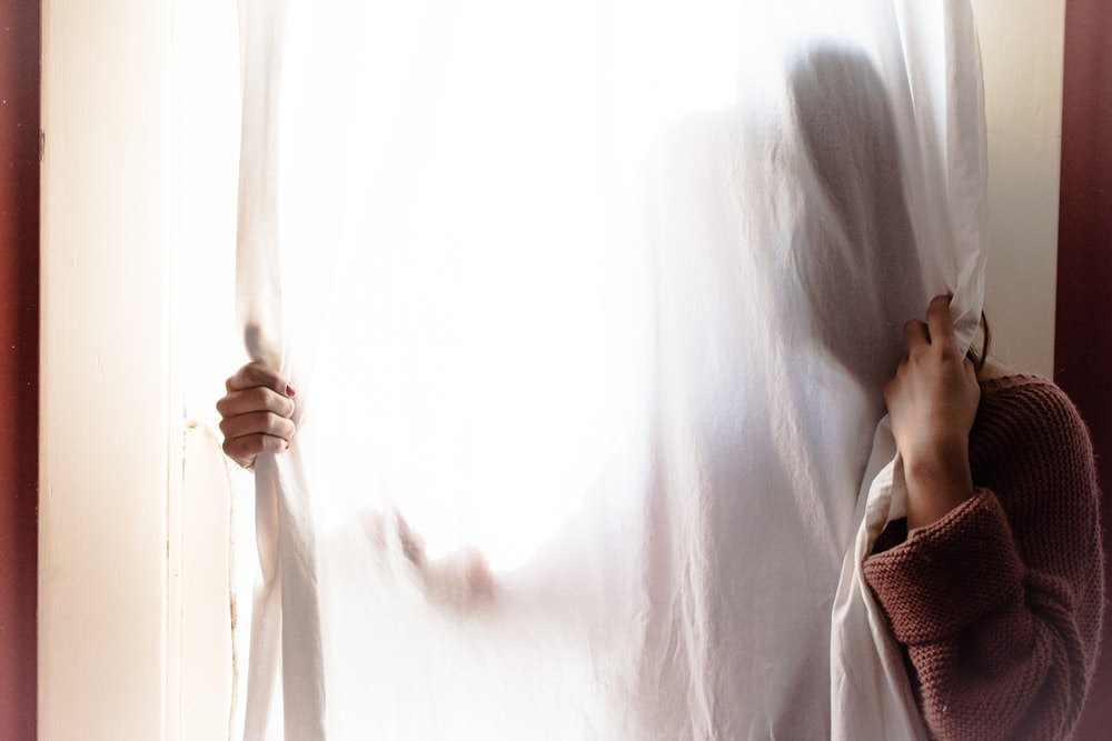 person hiding on white curtain