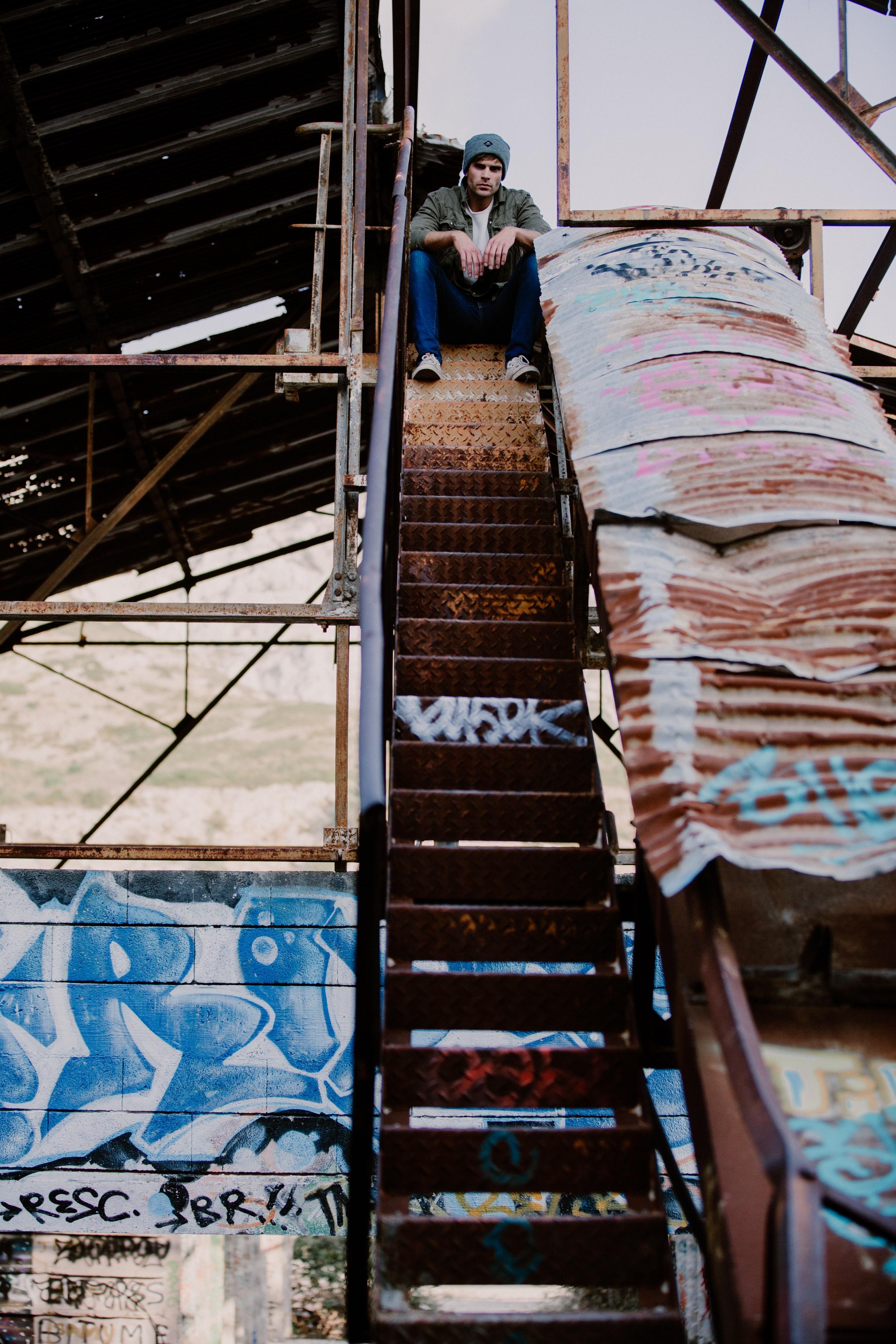 man sitting on stair during daytime