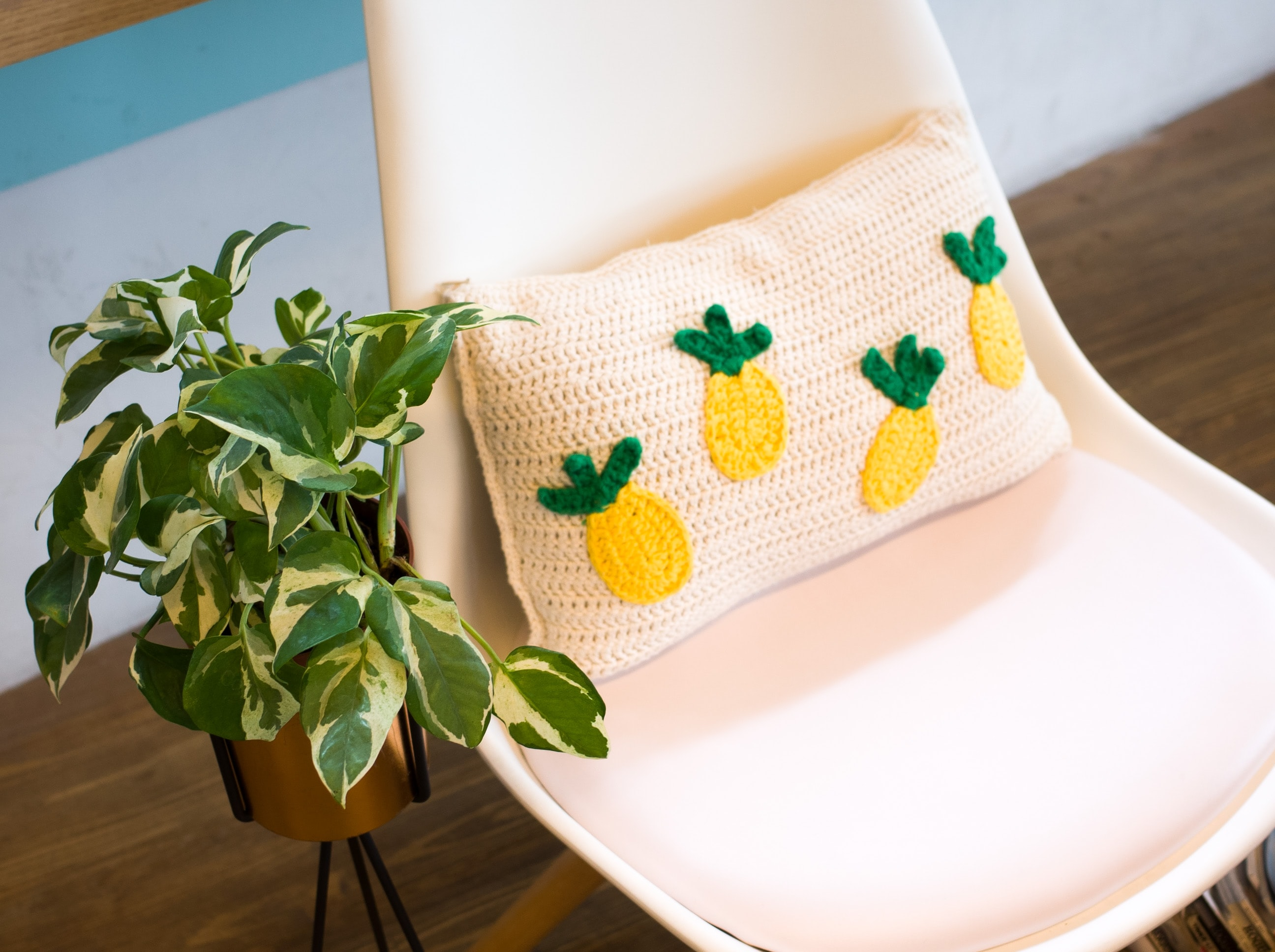throw pillow on chair beside plant on stand