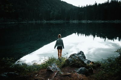woman standing on rock near body of water facing trees during daytime