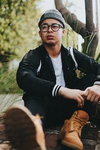 man wearing black jacket sitting near tree