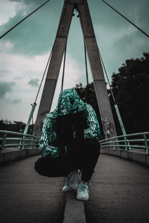 crouching person wearing track hoodie on bridge