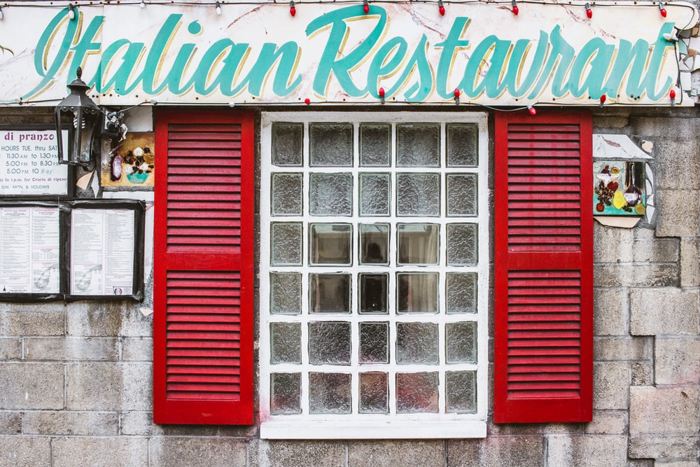 Italian restaurant signage under clear glass window panel