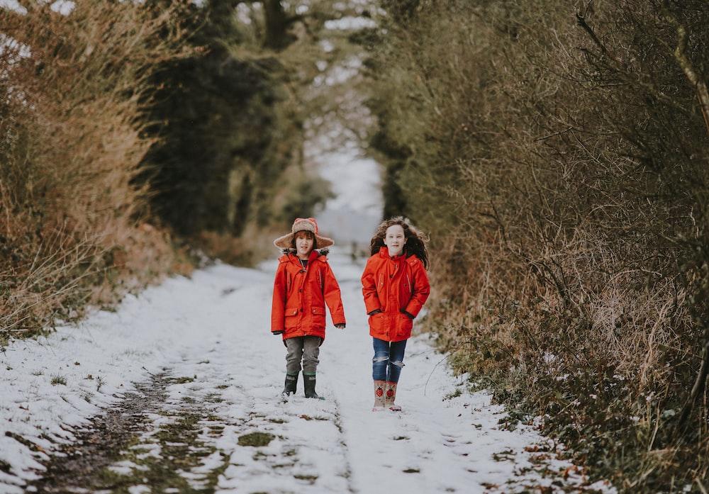 two children walking near bushes during winter