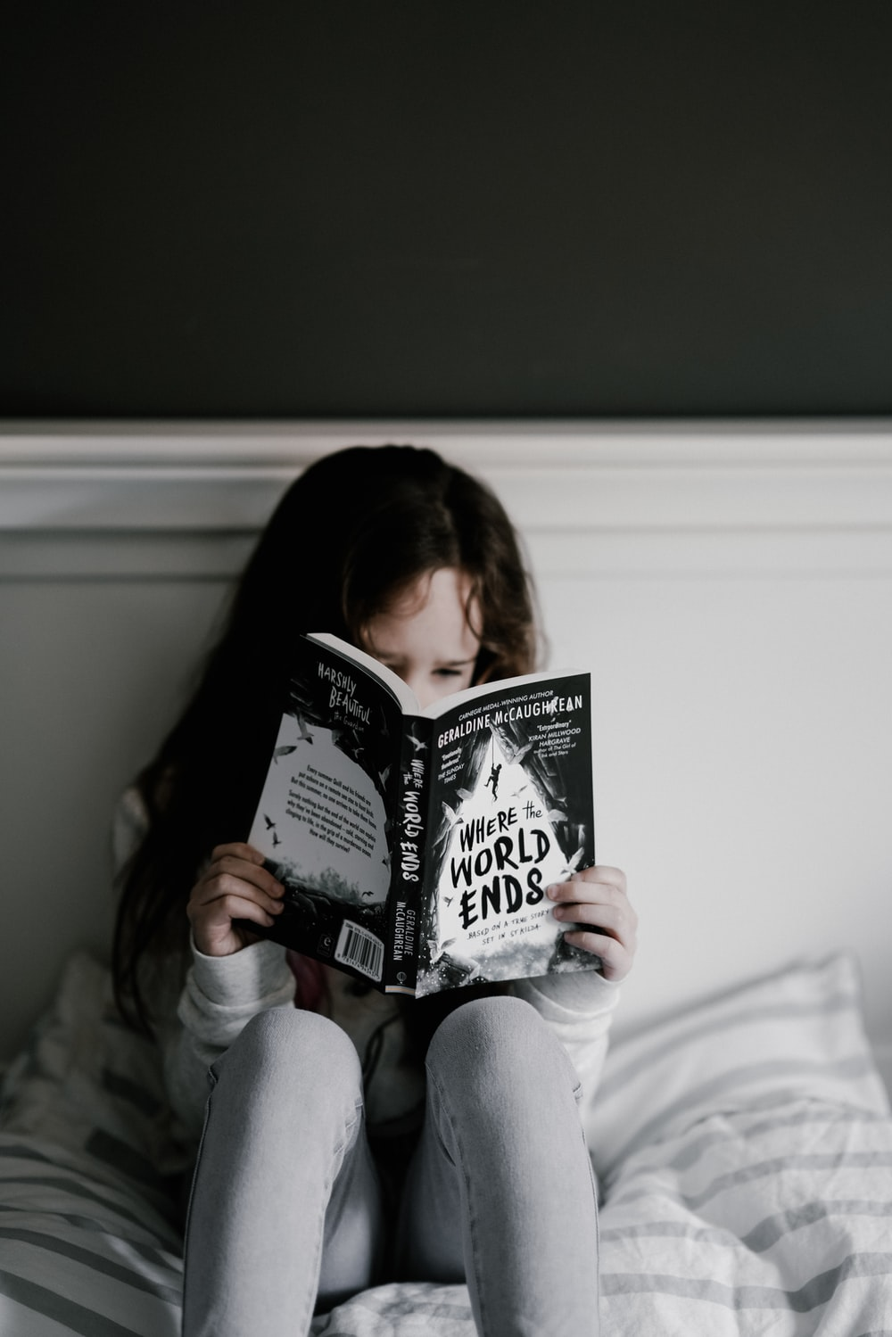 girl reading book on bed