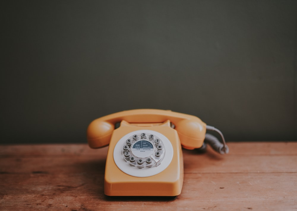 brown rotary dial telephone in gray painted room