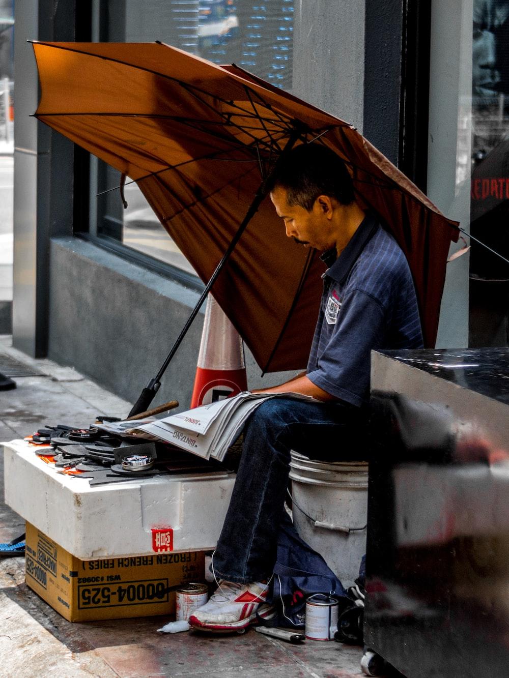 man sitting under brown umbrella