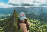 woman wearing gray cap standing near mountain