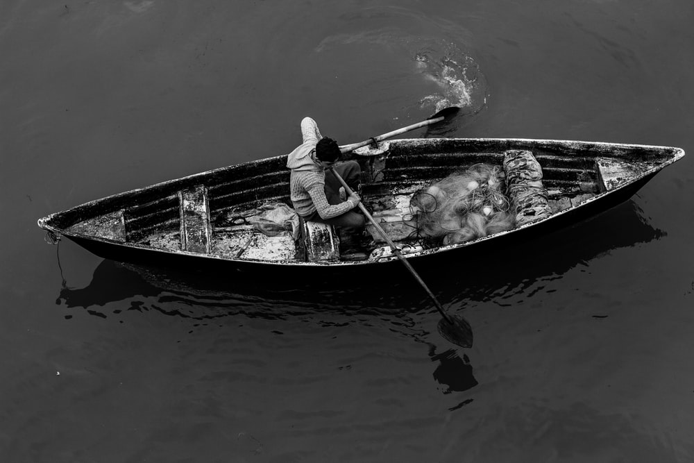 grayscale photo of man on canoe