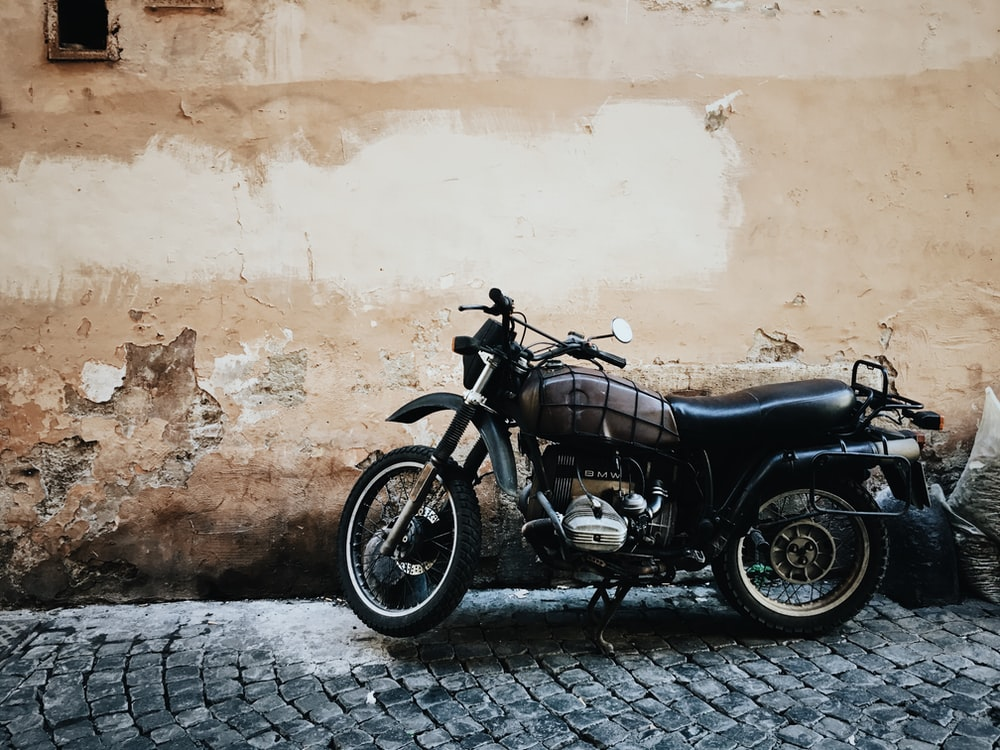 black and gray motorcycle parked on street beside wall at daytime