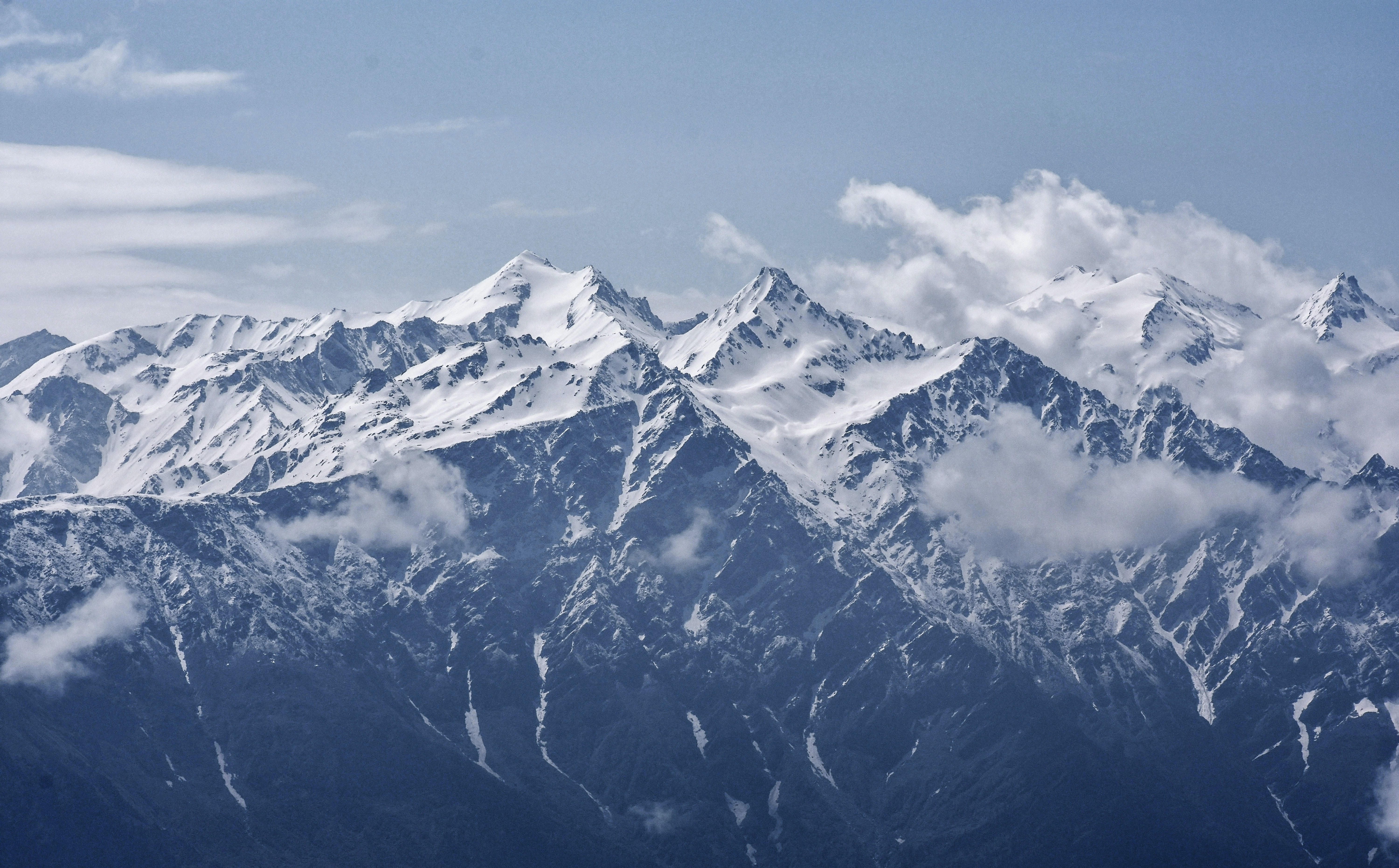 snow-covered mountains with white clouds during daytime