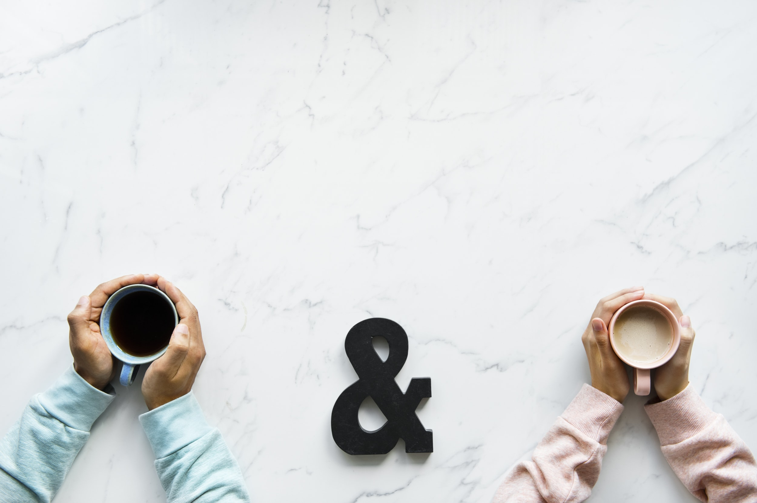 two person holding mugs with coffee