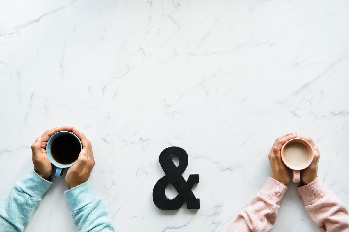 Photograph of two hands holding coffee at a marble table with an ampersand in between them.