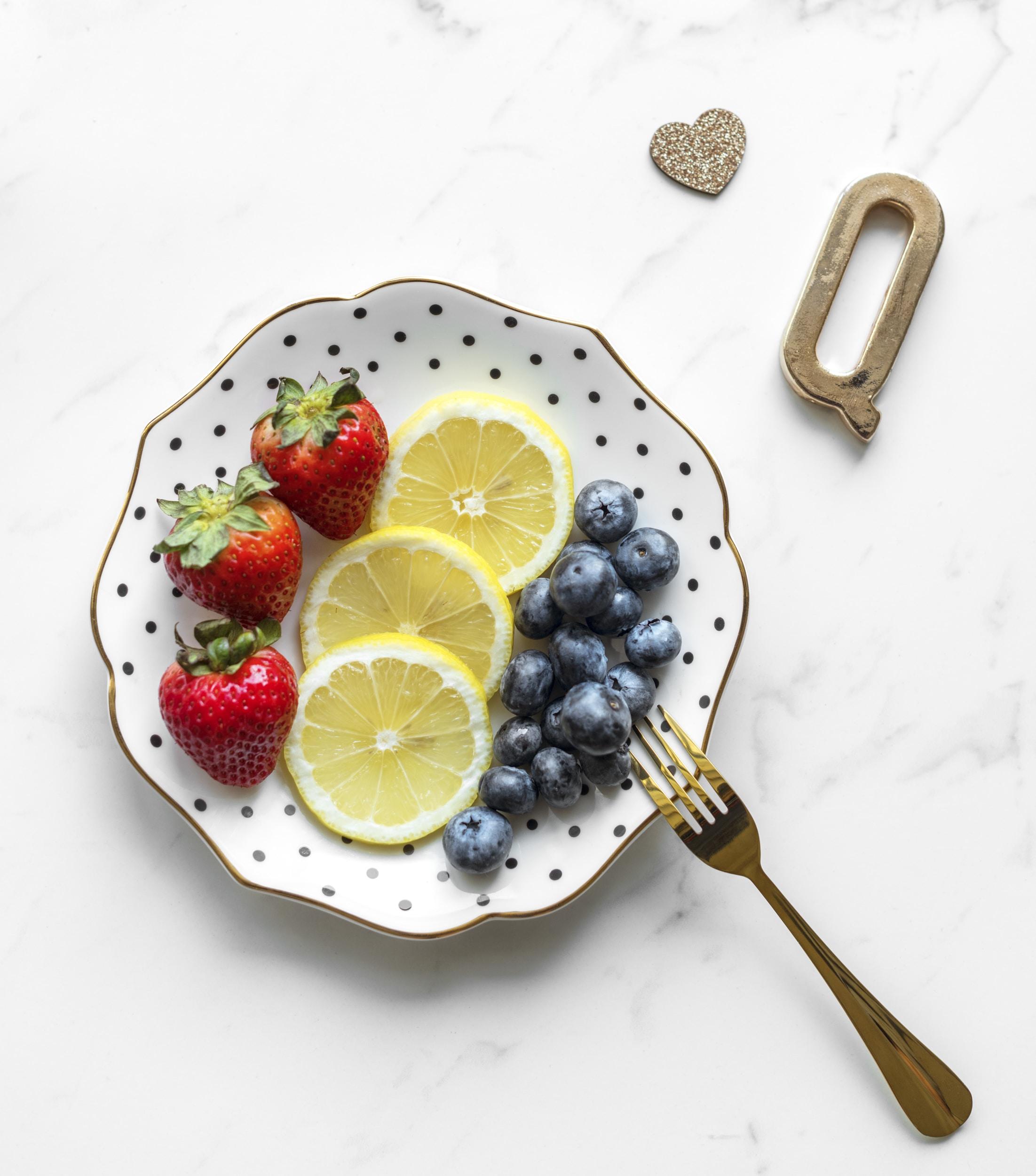strawberries, blueberries and sliced lemons on round white and black polka-dot ceramic plate