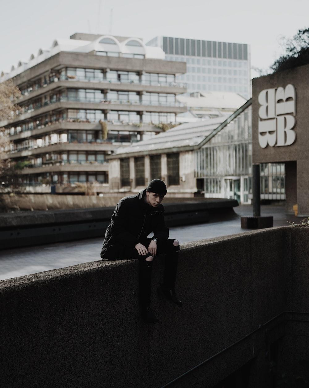 man sitting on concrete edge during daytime