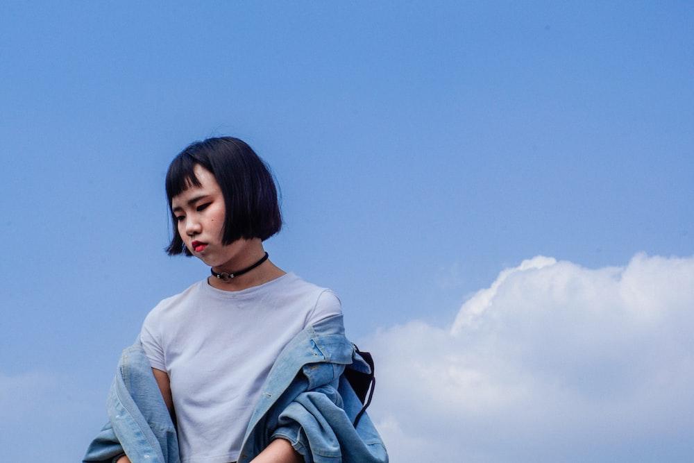 woman wearing blue denim jacket under cloudy blue sky