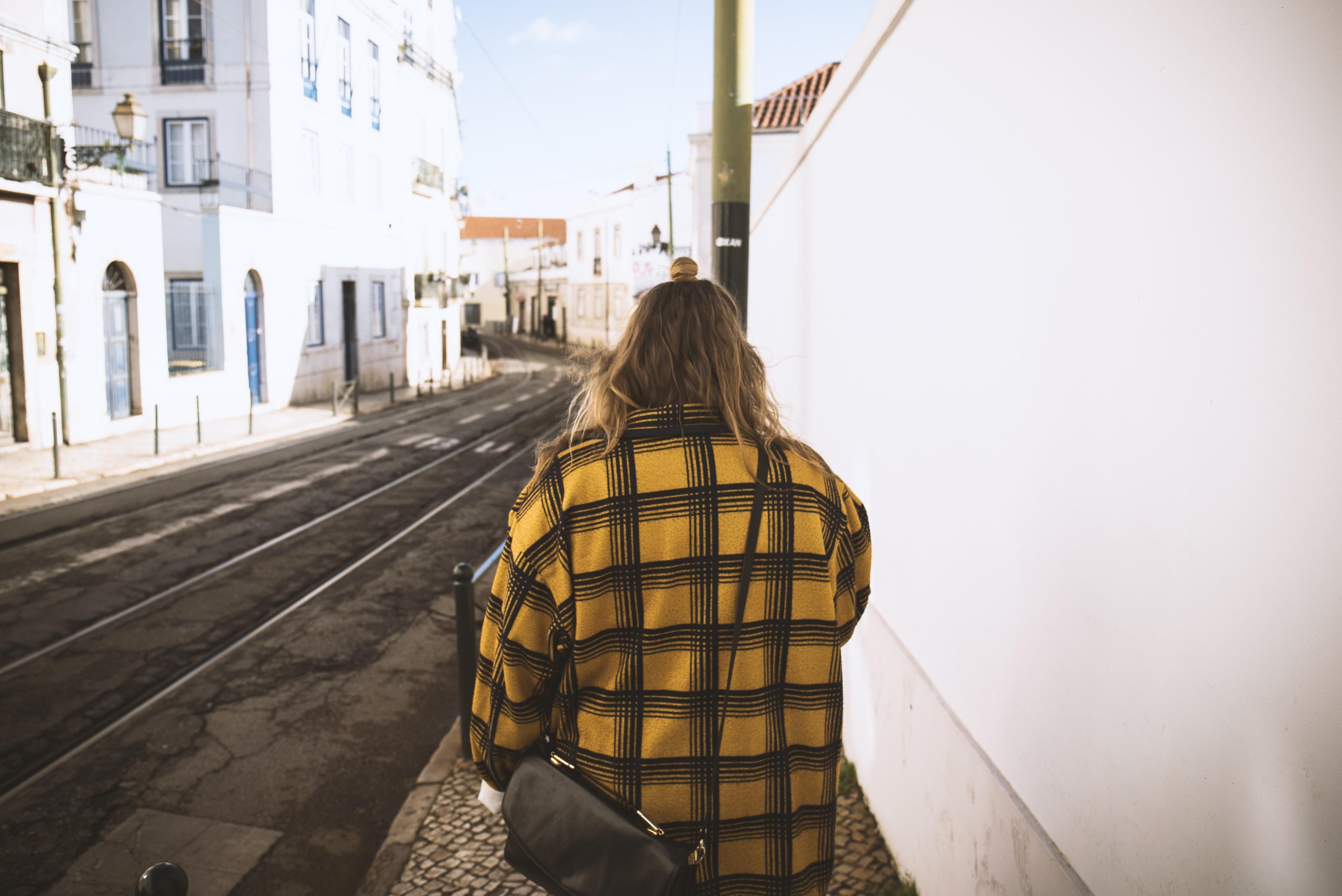 woman walking beside white concrete wall