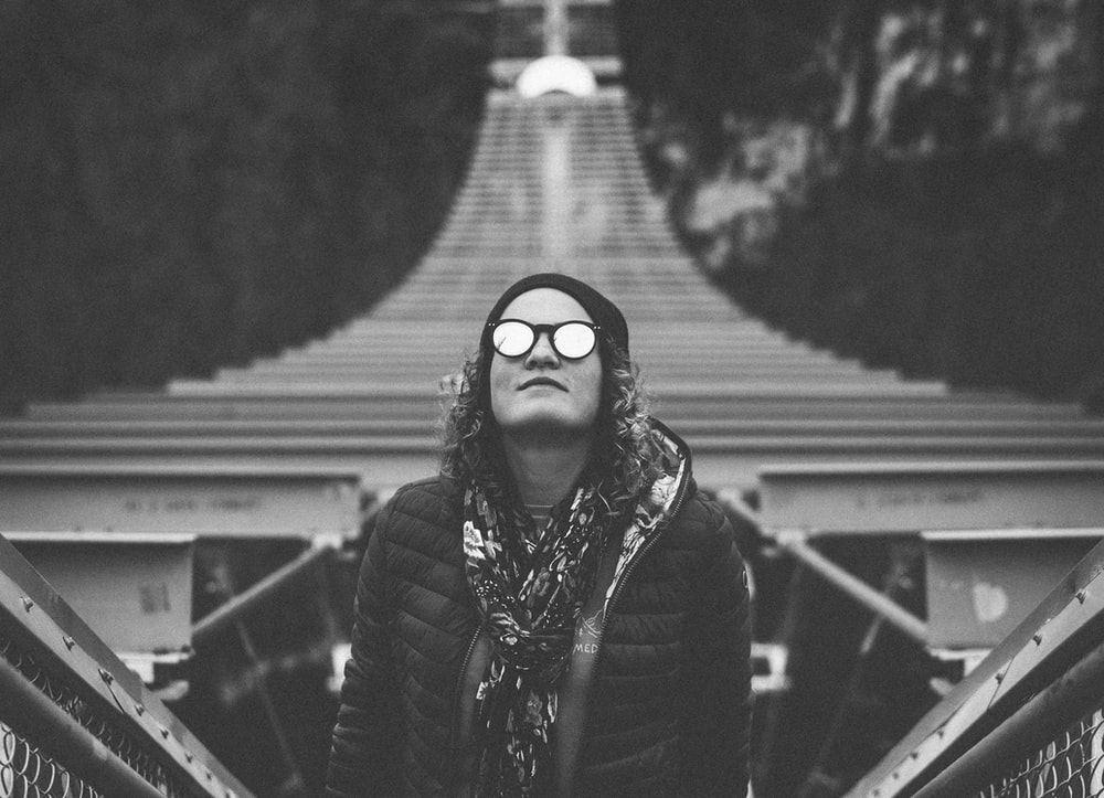 grayscale photography of woman standing while looking up on hanging bridge