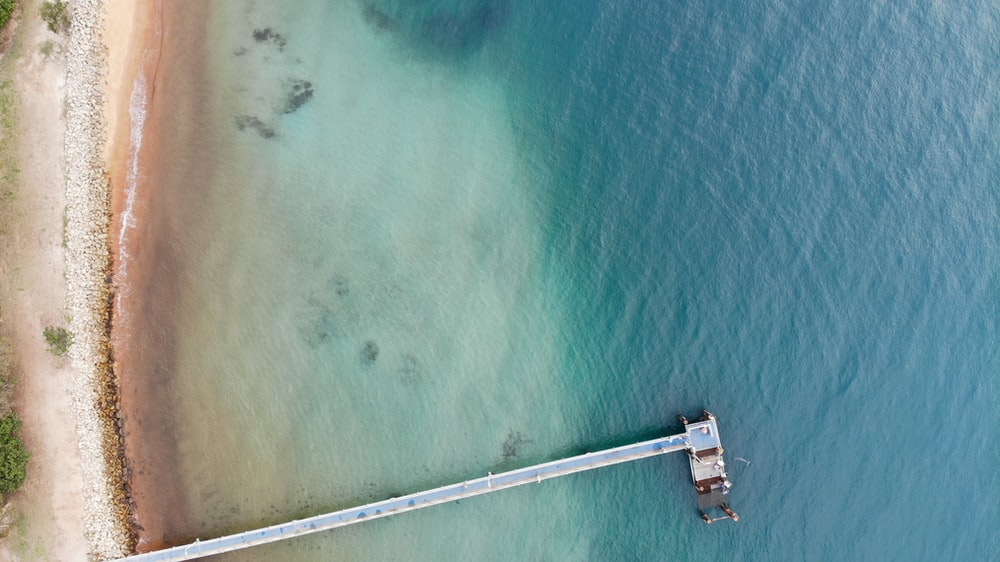 aerial photography of wooden dock on the ocean