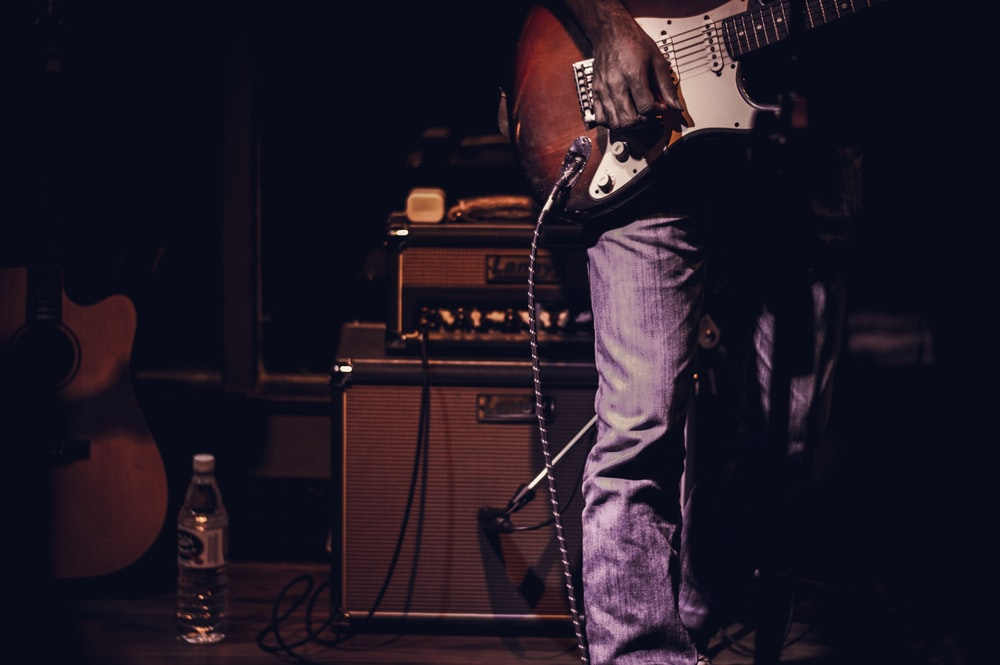 man playing guitar inside dark room