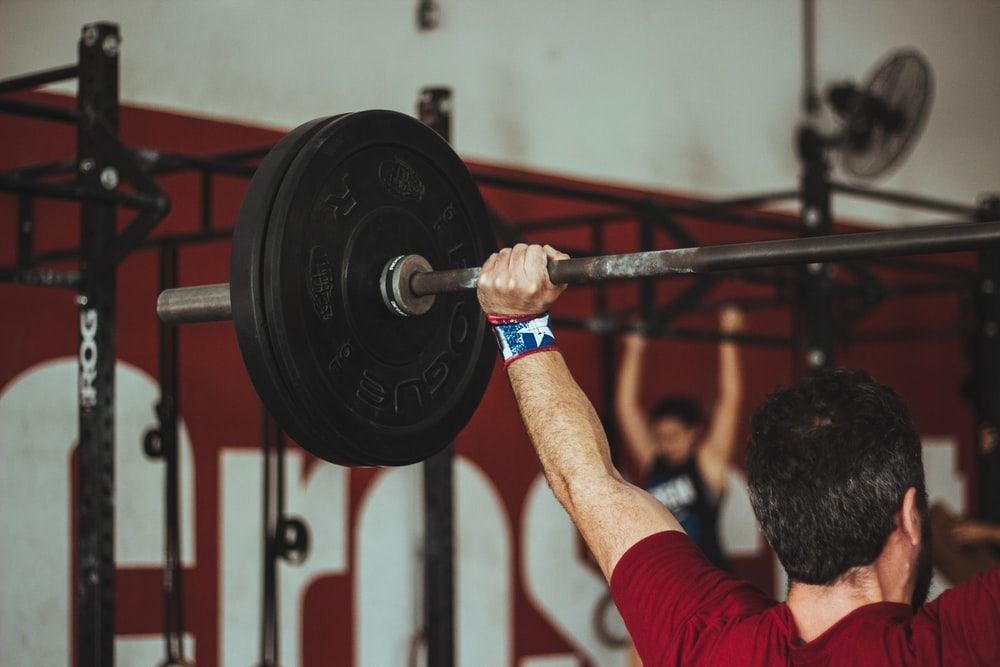 man carrying barbell at the gym