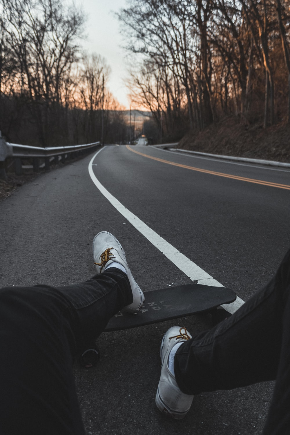 person sitting on road with longboard
