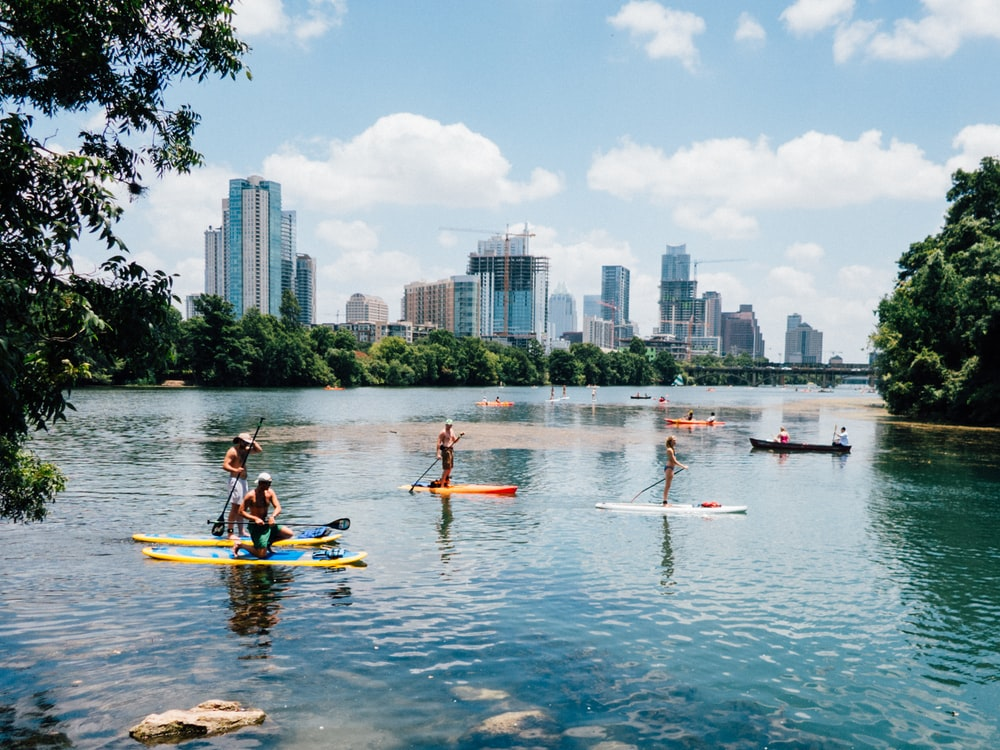 people riding paddle boards on the lake